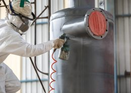 A coating specialist applies powder coating to chemical pipe